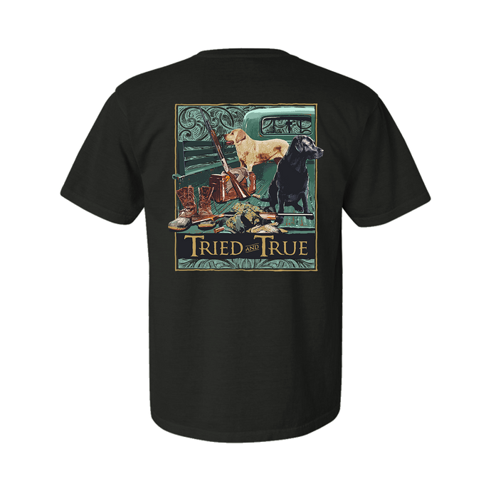 Printed on a Comfort Color granite/charcoal t-shirt with a back print of a yellow and black lab in the back of an old truck. With a set of ducks, gun, and boots to the left of the image.