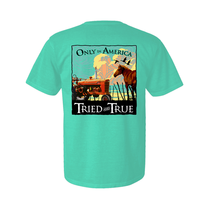 Printed on a Comfort Color chalky mint colored t-shirt the only in america shirt is a framed peaceful ranch scene. With a Horse on the right side and an old red tractor on the left.