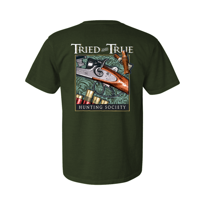 Printed on a Comfort Color moss colored t-shirt, a design containing an old side by side polished new and it's metal engraved dogs gleaming with wooden duck calls to the top right corner and shells in the bottom left. Framed with the Tried & True signature waves in the background and