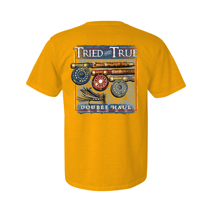 Printed on a Comfort Color citrus colored t-shirt the double haul fishing shirt has three cork handled fly rods, with a navy, red, and light blue reel from left to right. With a light blue fly in the bottom left of the framed imaged with