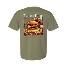 "Load image into Gallery viewer, Printed on a Comfort Color sandstone colored t-shirt the American classic burger is a fresh burger with lettuce, cheese, bacon, tomatoes and complimented with a coke, ketchup, and fries. It is framed with ""American Classic"" at the bottom and ""Tried & True"" at the top with the Tried & True signature waves in the background."