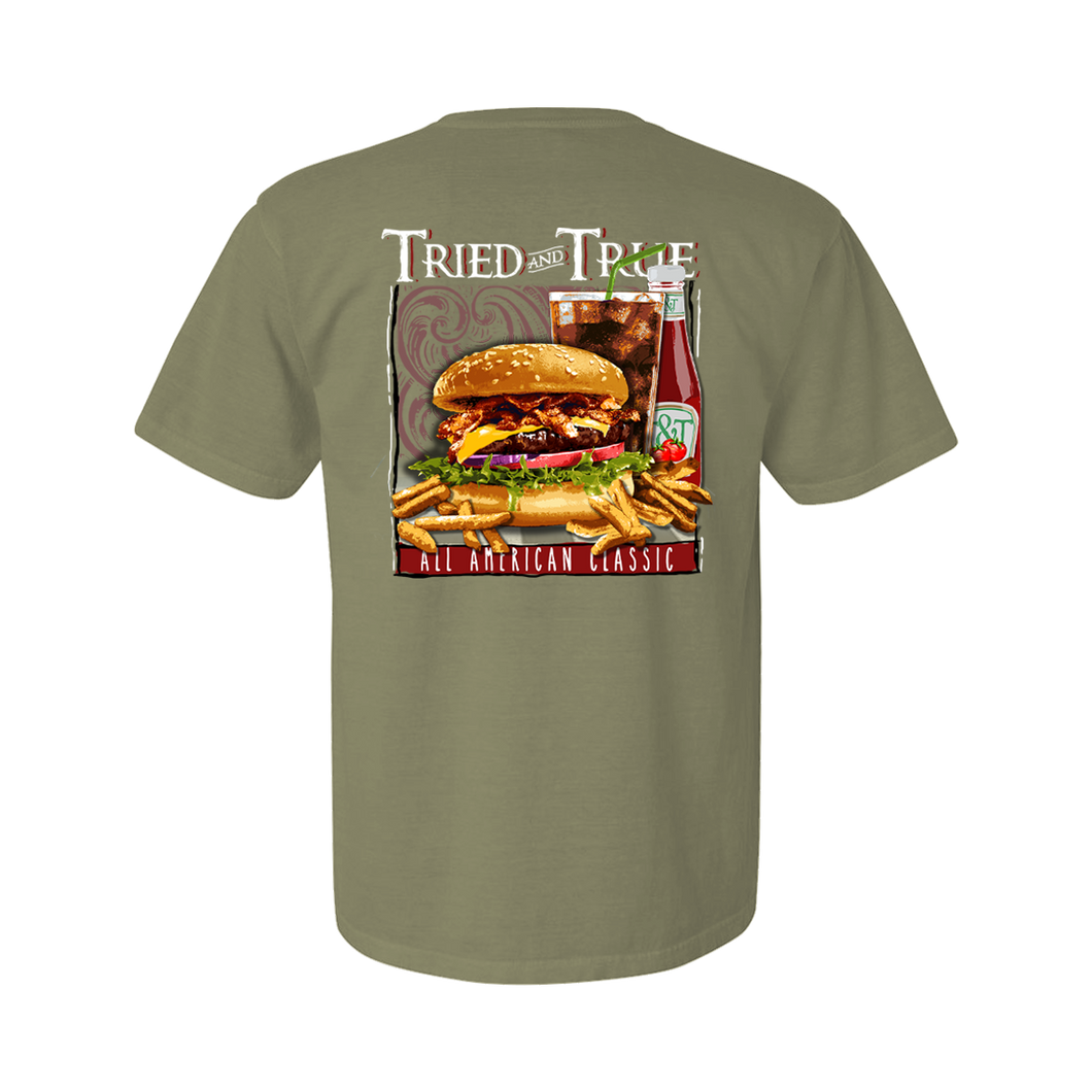 Printed on a Comfort Color sandstone colored t-shirt the American classic burger is a fresh burger with lettuce, cheese, bacon, tomatoes and complimented with a coke, ketchup, and fries. It is framed with