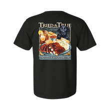 Load image into Gallery viewer, Printed on a Comfort Color pepper color colored t-shirt the Southern classic ribs and taters is a southern picnic design. With bright red bbq ribs with fluffy mashed potates, a side a corn beard, and a refreshing sweet tea. With a black lab puppy on the right with the Tried & True signature waves in the background.