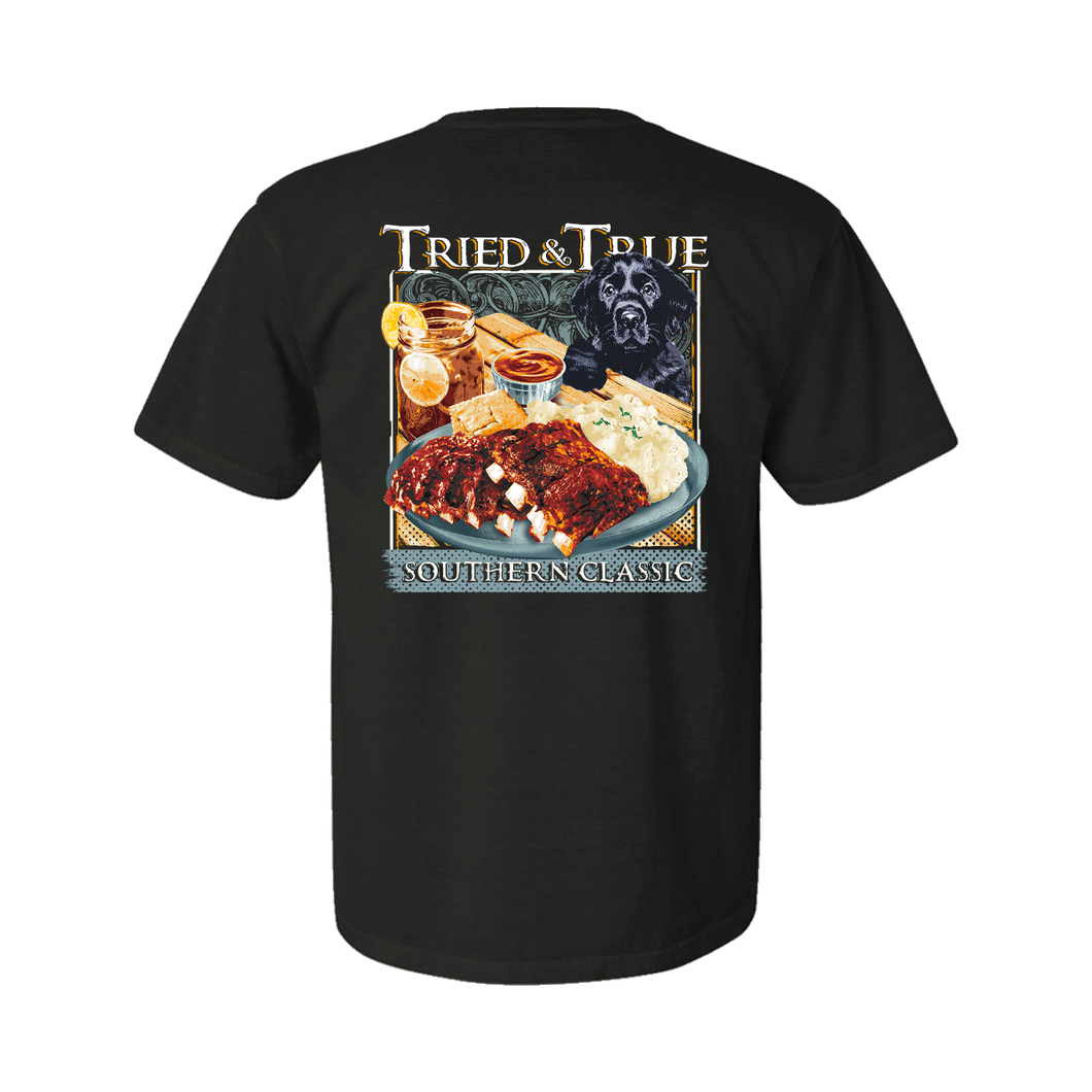 Printed on a Comfort Color pepper color colored t-shirt the Southern classic ribs and taters is a southern picnic design. With bright red bbq ribs with fluffy mashed potates, a side a corn beard, and a refreshing sweet tea. With a black lab puppy on the right with the Tried & True signature waves in the background.