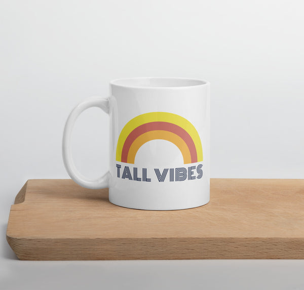"White, ceramic 11 oz coffee mug with a rainbow and the phrase ""Tall Vibes"""