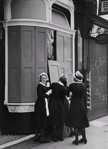 "George Rodger - ""Nippies"" (Lyons teashop waitresses) remove protective shutters from windows in early morning. London during the Blitz, 1940"