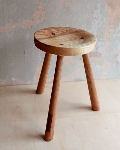 Large three legged wooden stool with a concave seat