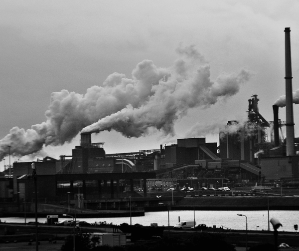Black and white image of a working factory with smoking chimneys