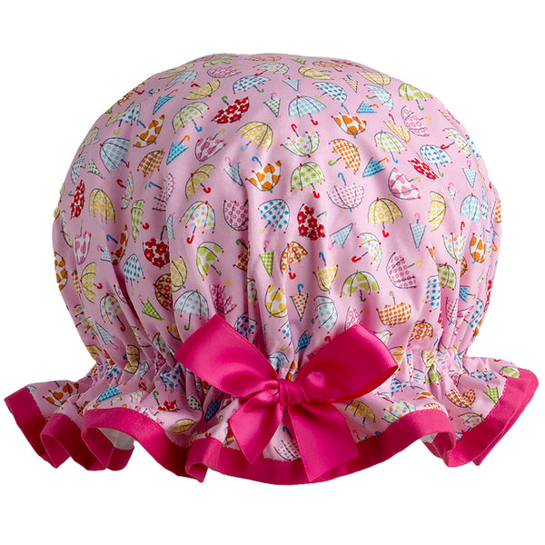Vintage style, women's large cotton shower cap. Frilled edge, small multicoloured umbrellas print on pink background with bright pink trim and matching satin bow.