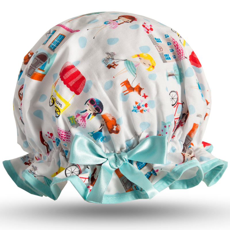 Vintage style women's large cotton shower cap.  Frilled edge, colourful Parisian style print of women walking little dogs, cycling, ice cream cars, houses and trees on a white background with aqua trim and bow.