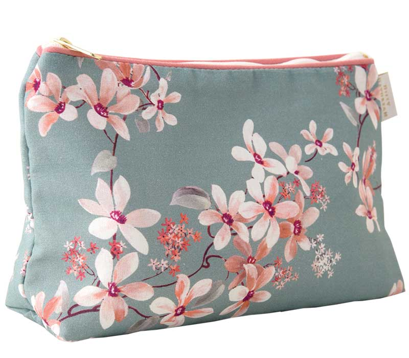 Zip top traingular shaped cotton sponge bag. Peach and cream trailing floral print on a greeny grey background, trimmed in peach with white zip. Waterproof lining.