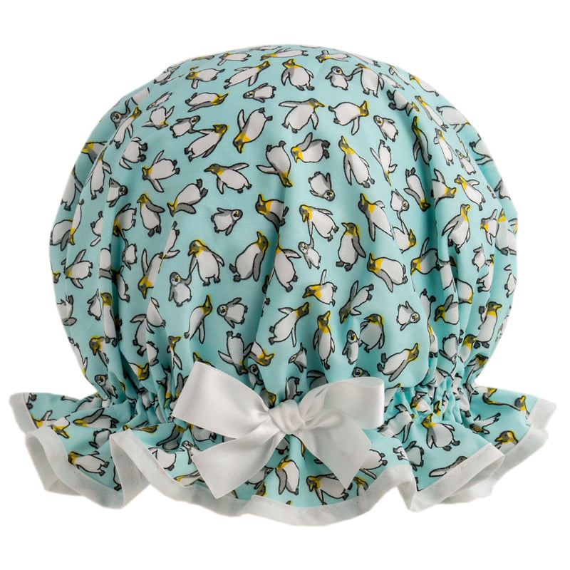 Vintage style, women's large cotton shower cap. Frilled edge, pale aqua background with cute penguin print. Trimmed in white cotton and matching white satin bow.