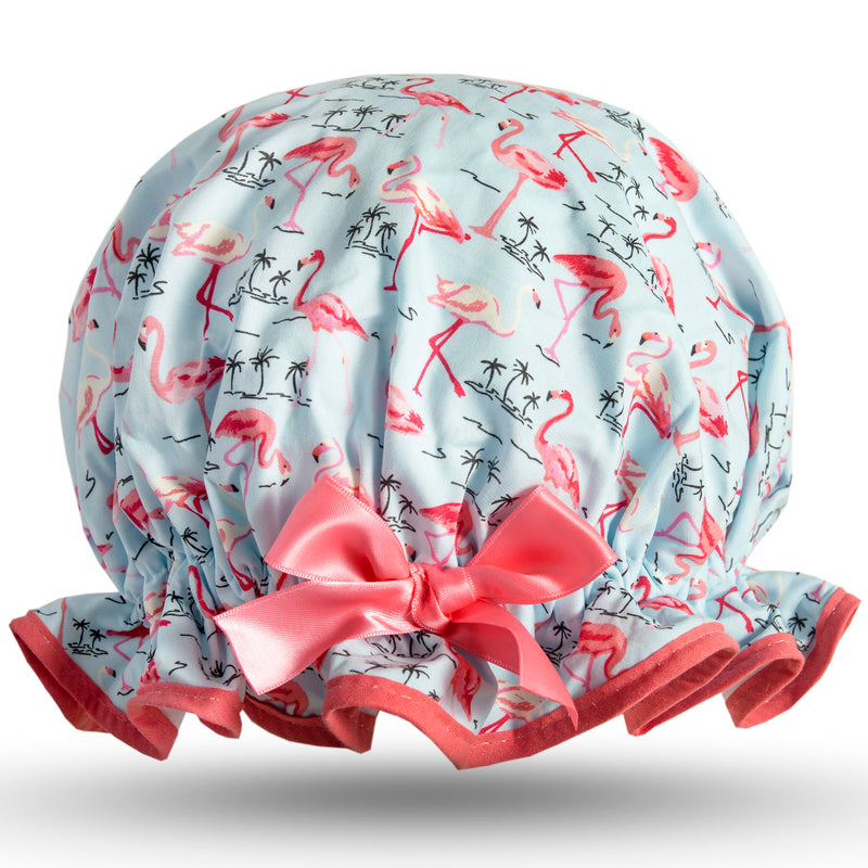 Vintage style women's large cotton shower cap.  Frilled edge, pink flamingos with small black palm tree outline on pale blue background.  Coral trim and satin bow.