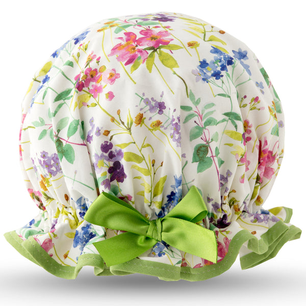 Vintage style, women's large cotton shower cap. Frilled edge, multicoloured meadow print in blue, pink and purple on a white background.  Trimmed in pale green with matching satin bow.