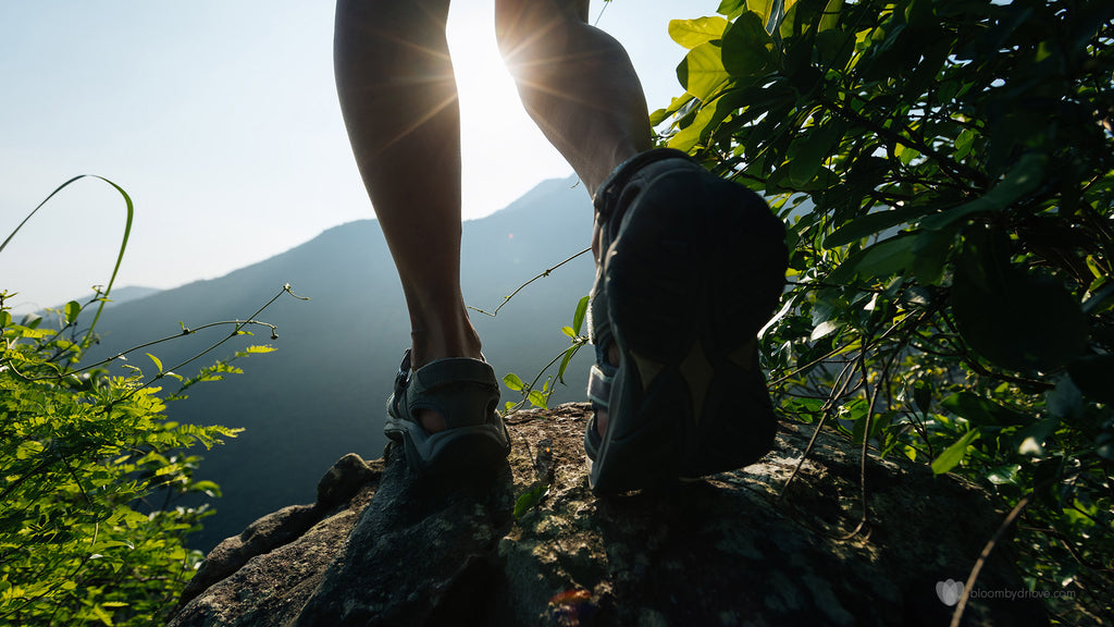 runner's legs and feet at the top of a hill