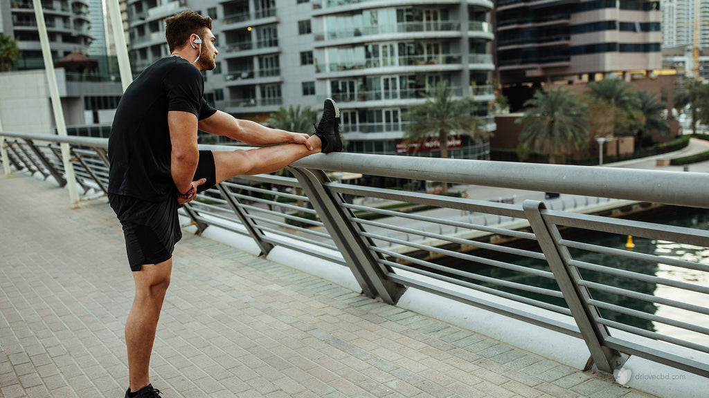 healthy man with headphones stretching outside before a run through the city