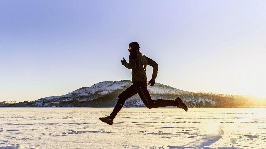outdoor photo of healthy man running across the snow during a bright sunny winter day