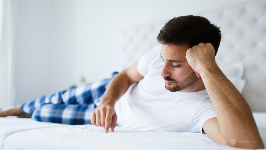 shot of young man in bed struggling with mental health laying in bed showing no motivation