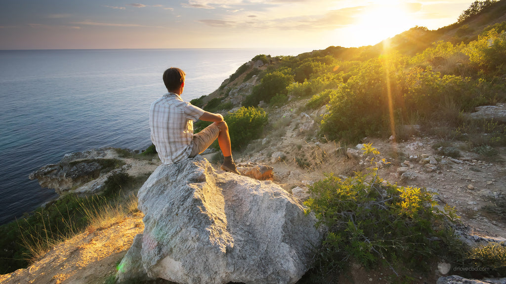 young man with anxiety outdoors by the sea enjoying a sunrise during a quiet peaceful morning