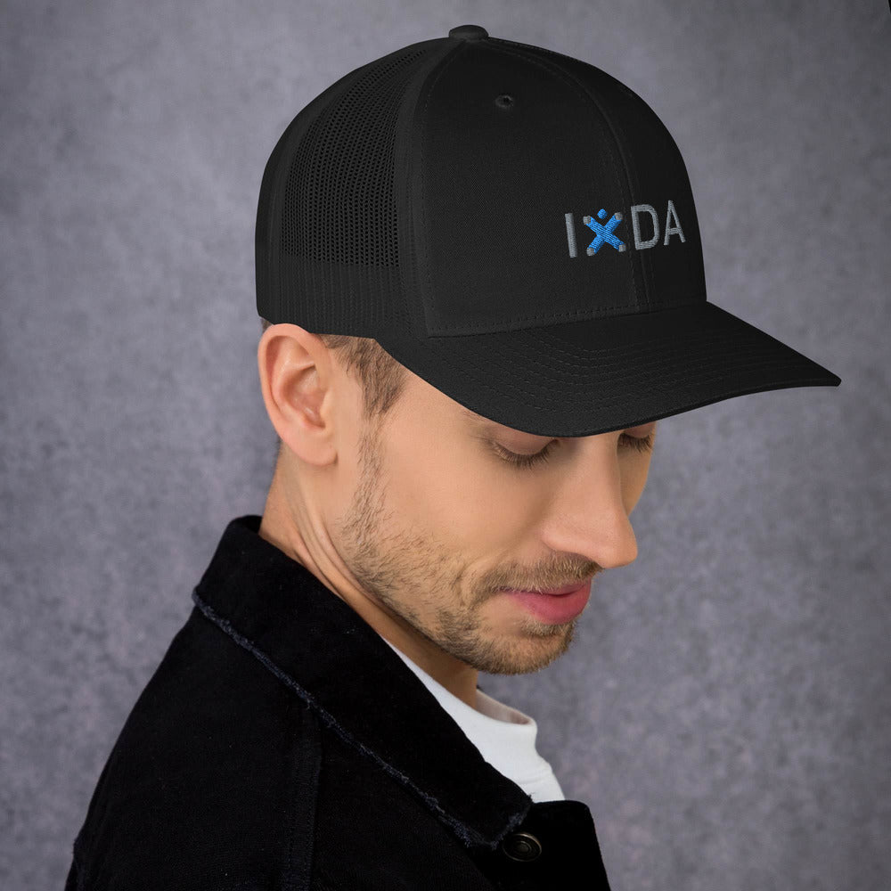 Man wearing black trucker cap. Hat has grey and blue embroidered IxDA logo.
