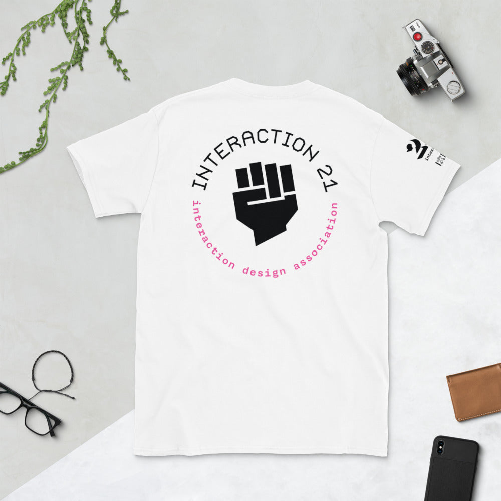 White T-shirt shot from above with pink and black 'Social Injustice' graphic across the back. Glasses, camera and cellphone are also on table.