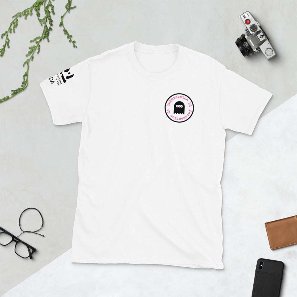 White T-shirt shot from above with pink and black 'Social Injustice' graphic on left front. Black Interaction 21 and IxDA logos on left sleeve. Glasses, camera and cellphone are also on table.