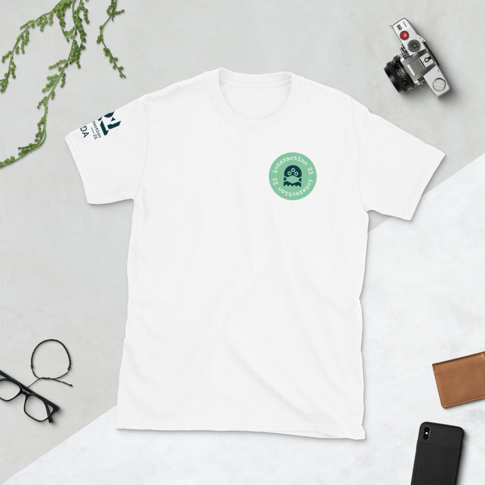 White T-shirt shot from above with green and black 'Virus' graphic on left front. Black Interaction 21 and IxDA logos on right sleeve.Glasses, camera and cellphone are also on table.