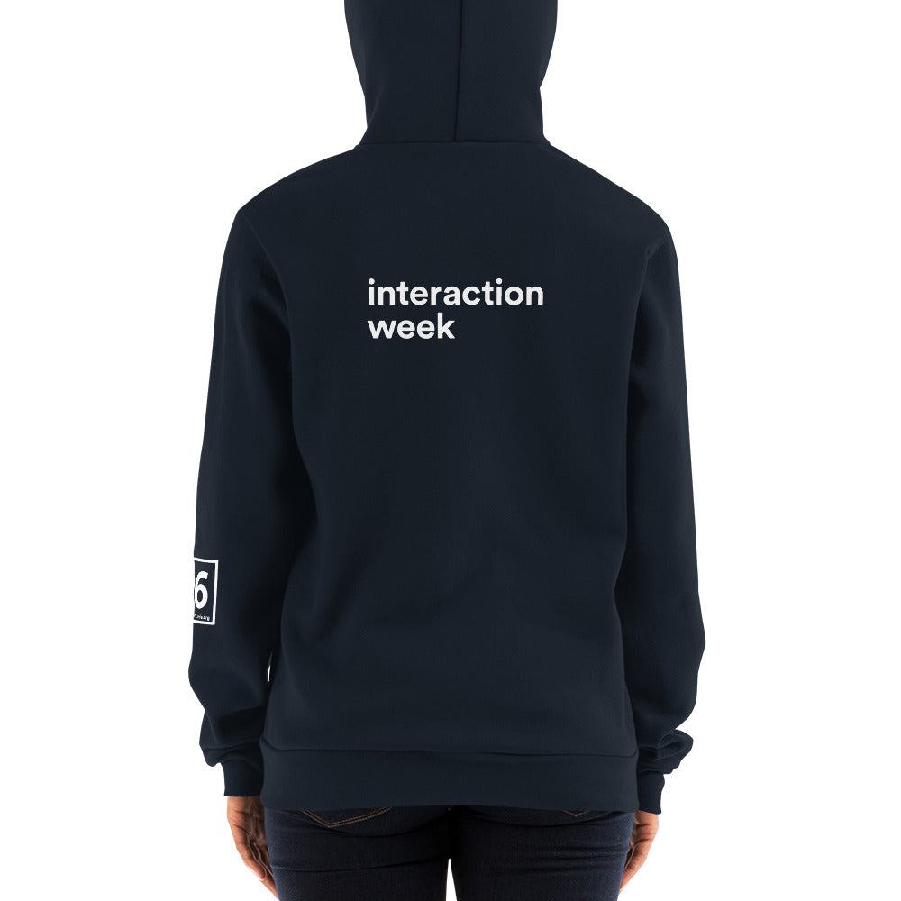 Person shot from the back in navy hoodie with white Interaction Week type across the back and Interaction q6 logo on left sleeve.