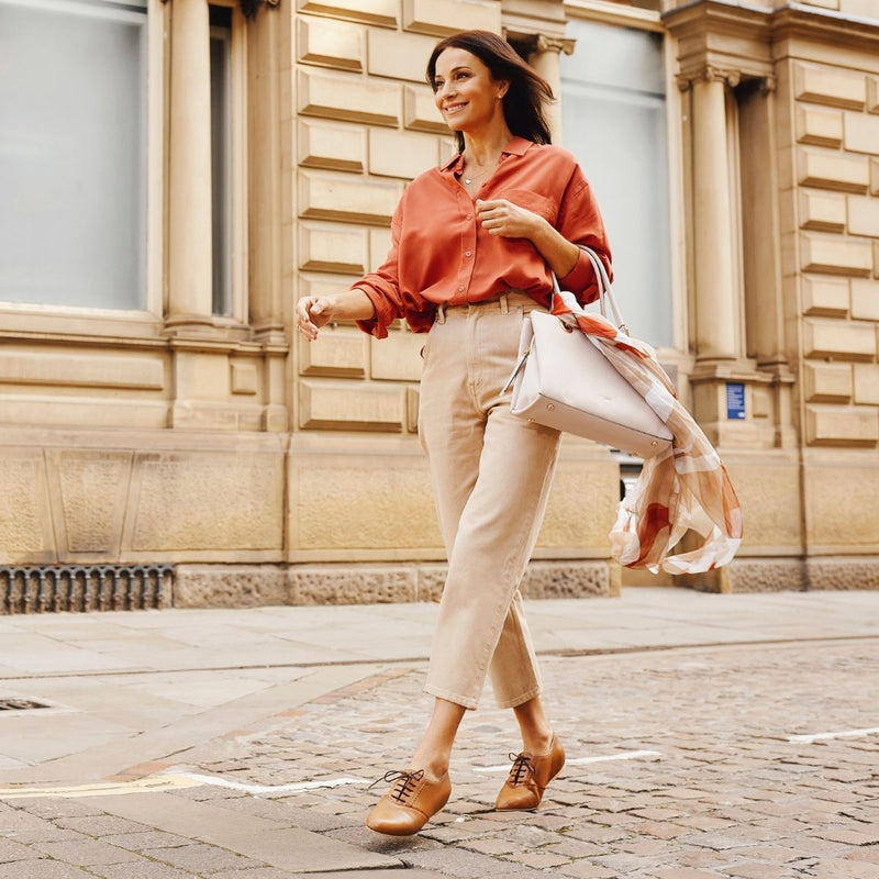 woman walking down the street in tan leather shoes