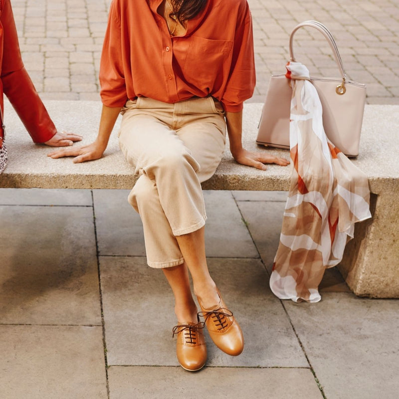 woman sitting on a bench in red shirt and brogue shoes