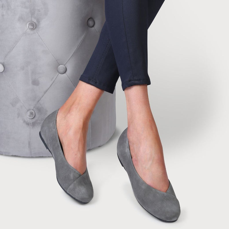 calla charlotte grey suede flat shoes for bunions as shown on a model who is sitting down on a grey chair