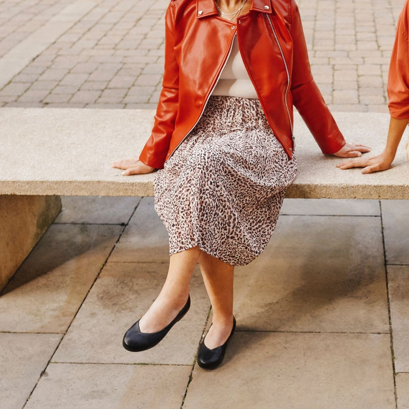 woman siting on bench in black shoes, leopard skirt and red jacket