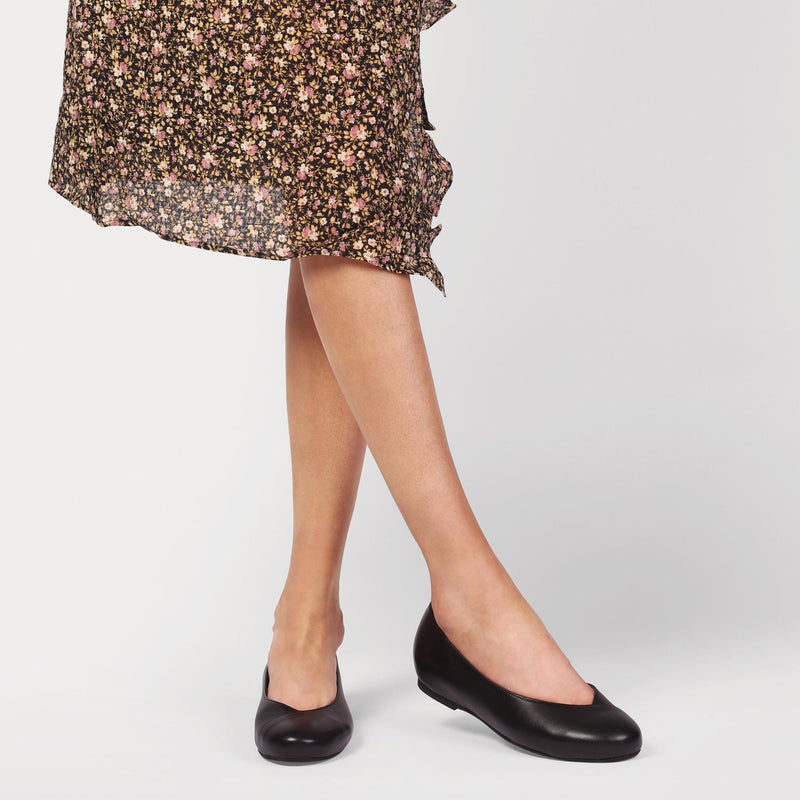 woman wearing black leather shoes and a dress with a flower pattern