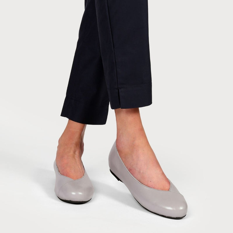 grey leather flats on crossed legs in navy trousers