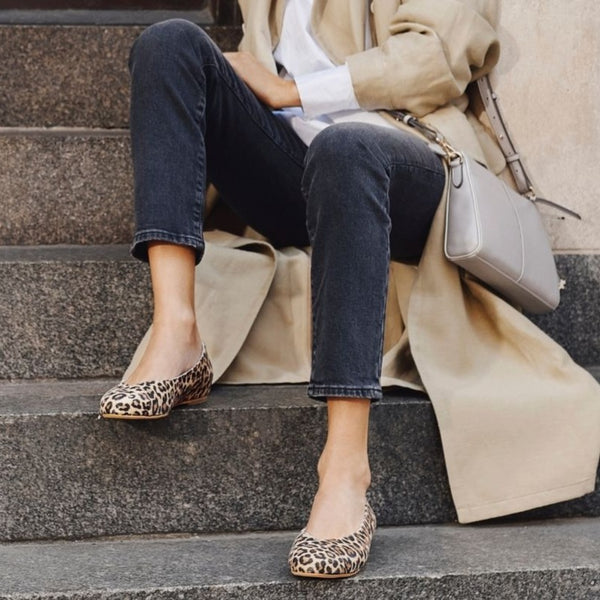 woman sitting on the stairs in leopard shoes