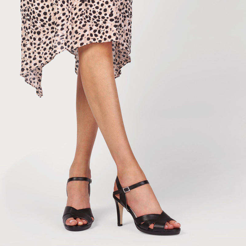 heeled black sandals shown on a model