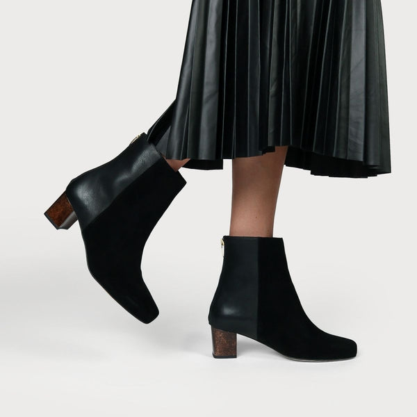 black leather suede boots worn with a black skirt