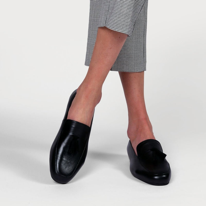 black leather loafers worn on crossed legs