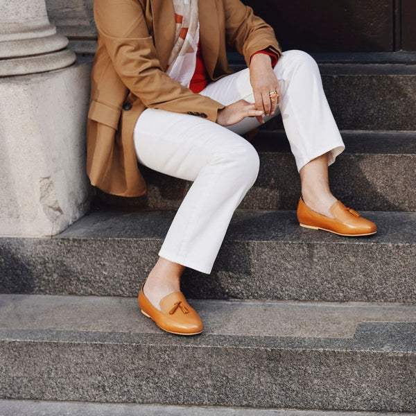 woman sitting on the stairs in tan leather loafer shoes and white trousers