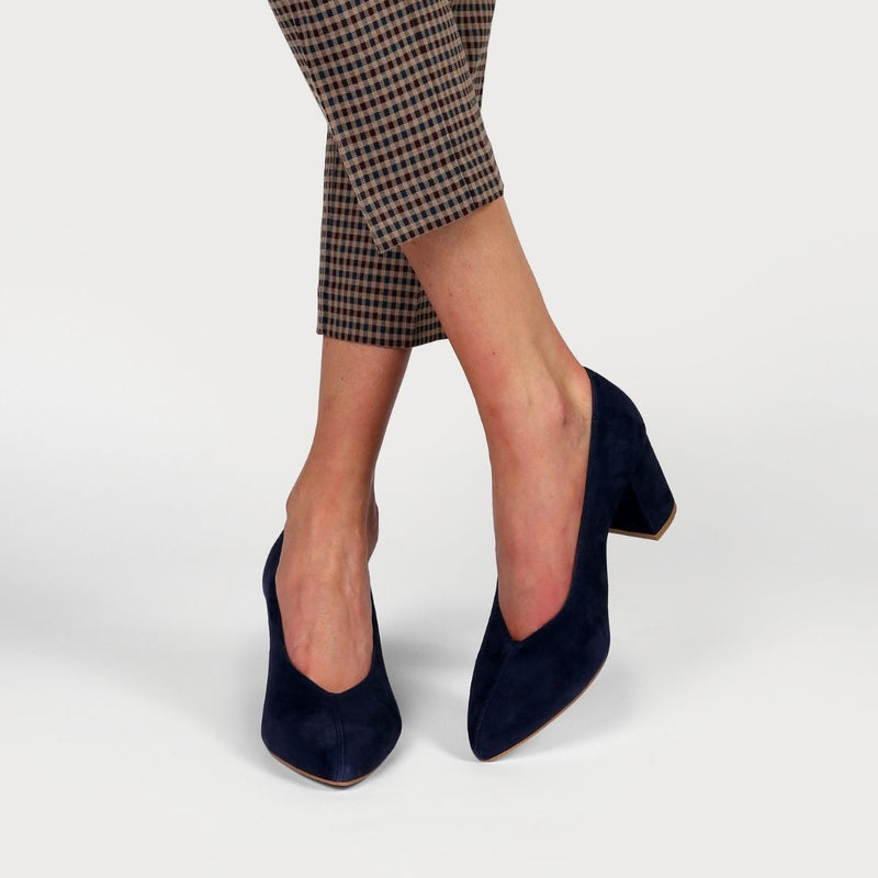 navy suede block heel worn on crossed legs