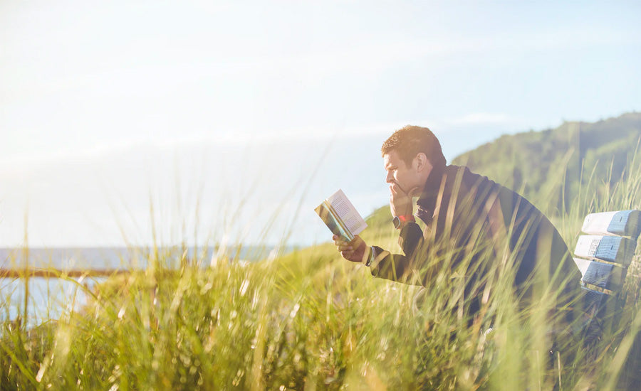 man reading book by the sea in field