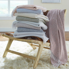 Stack of Terzo Throw by Sferra on a chair