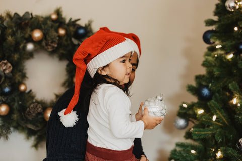 Child helping decorate a Christmas Tree. Let the Spirit of Christmas Heal the World