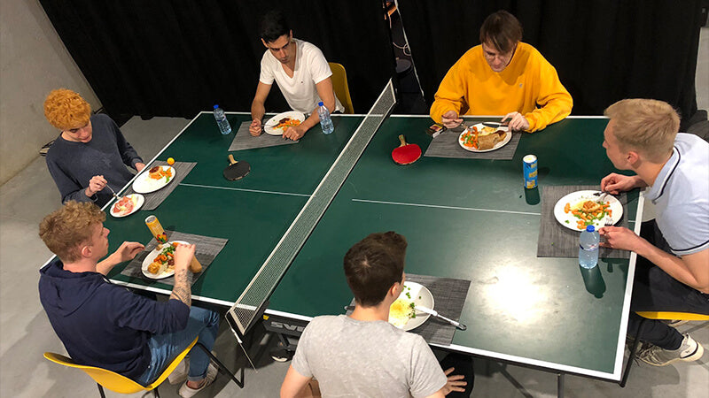 Sector One team eating dinner at the at the Qallo Esports Performance Center Ping Pong table