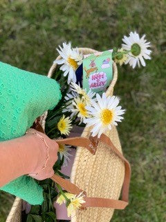 Lifestyle image of the product in a basket of daisies