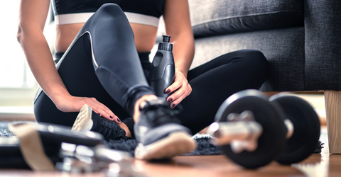 Home workout, weight training and fitness exercise concept. Woman in sportswear sitting in living room with gym equipment and dumbbell holding water bottle.