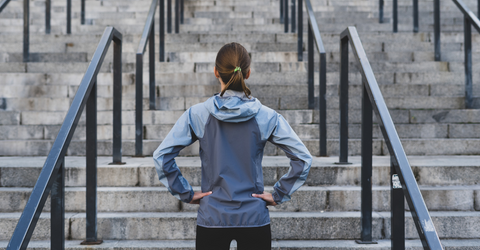 Young adult sporty woman looking at stairs, preparing to training