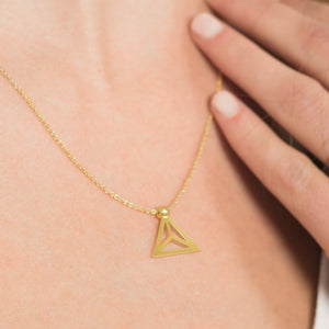 Yoga inspired gold necklace. The jewel stylises the Padmasana pose in an essential and geometric way. Sliding pendant.