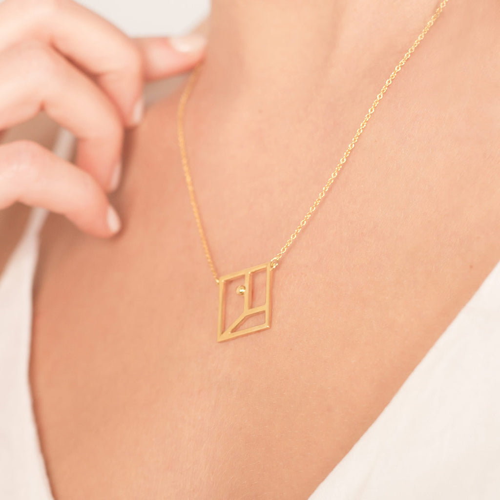 Yoga inspired gold necklace. The jewel represents the warrior one position. Essential and geometric style.