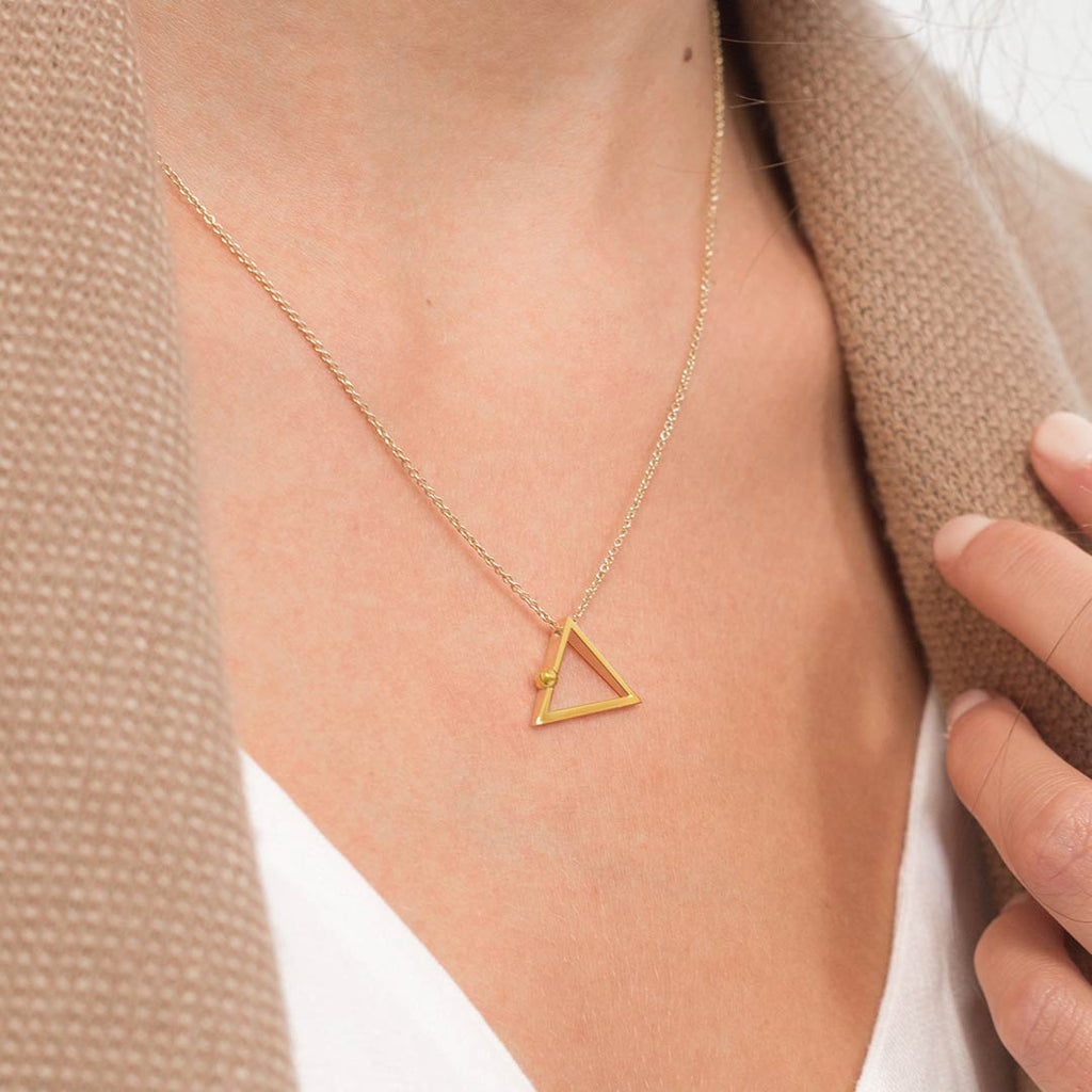 Yoga inspired gold necklace. The jewel stylises the Adho Mukha pose in an essential and geometric way. Sliding pendant.